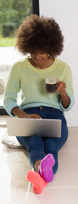 A woman drinking coffee and creating images on her laptop