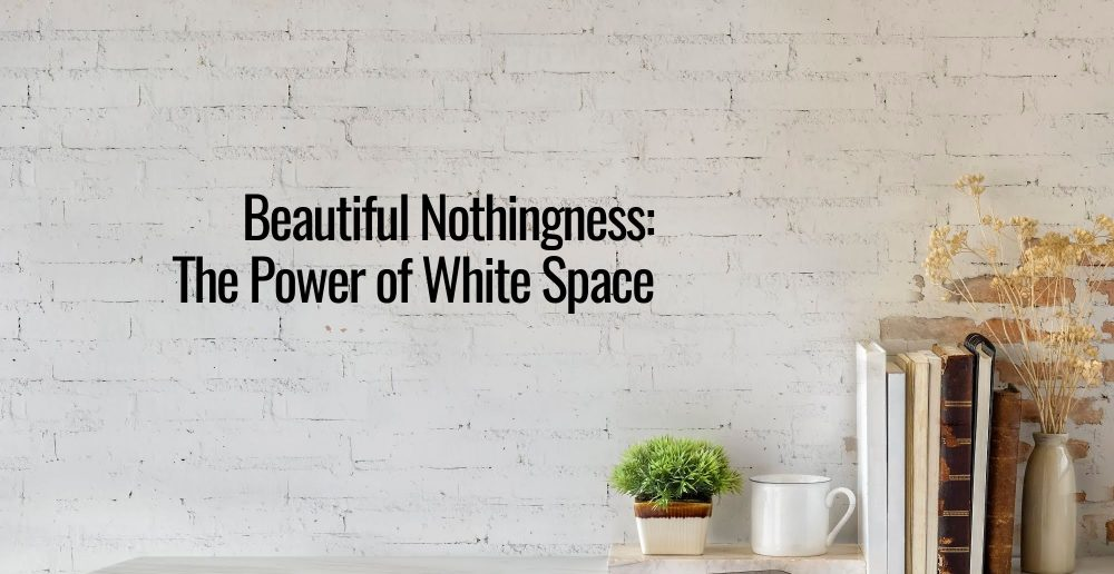 White brick background with a text that says beautiful nothingness the beauty of white space beside it is a small plant and a stack of books